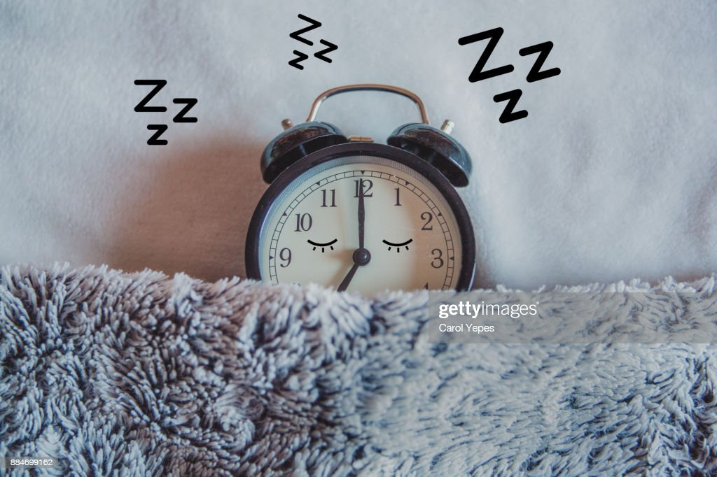 Alarm clock sleeping in bed : Stock Photo