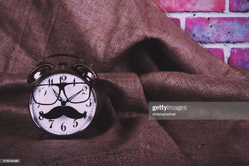 Alarm clock with a black hipster mustache Vintage Retro Filter. : Stock Photo