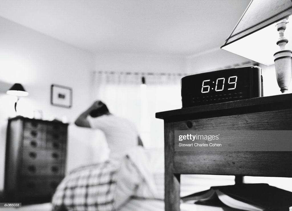 Alarm clock with man getting out of bed in background : Stock Photo