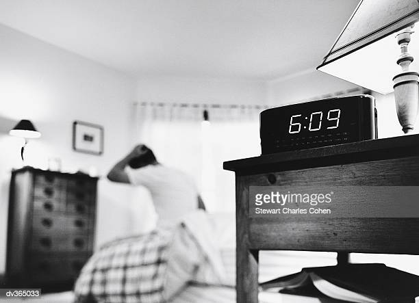 Alarm clock with man getting out of bed in background