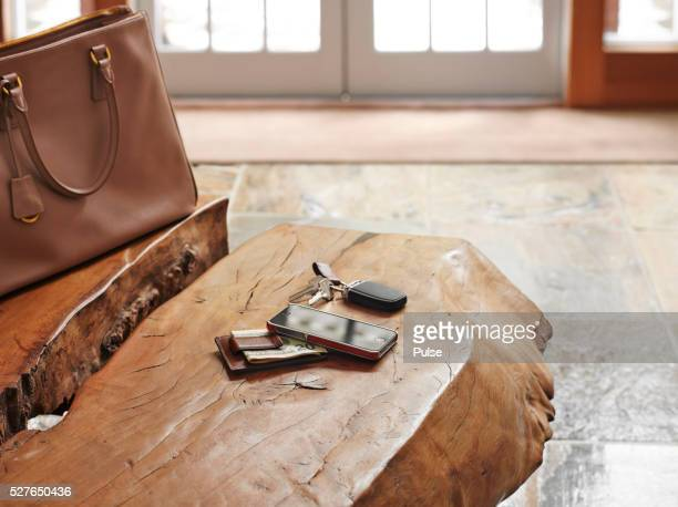 Alarm device with cell phone, US currency and bag on table