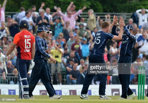 Alasdair Evans of Scotland is congratulated by his team mates after tacking the wicket of David Willy of England during the One Day International...