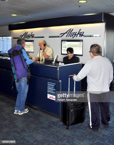Alaska Airlines gate agents assist passengers preparing to depart San Francisco International Airport