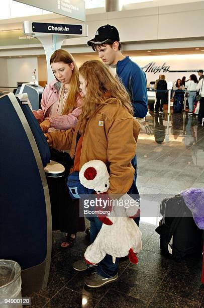 Alaska Airlines passenger Laura Visscher center checks in at a self service kiosk with friends Annette left and Ben Fosgaten in Ted Stevens...