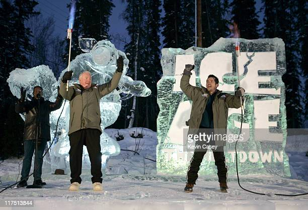 Alaska Governor Frank Murkowski left and Actor John Leguizamo raise their arms after they used torches to melt the ice ribbon after riding sled dogs...
