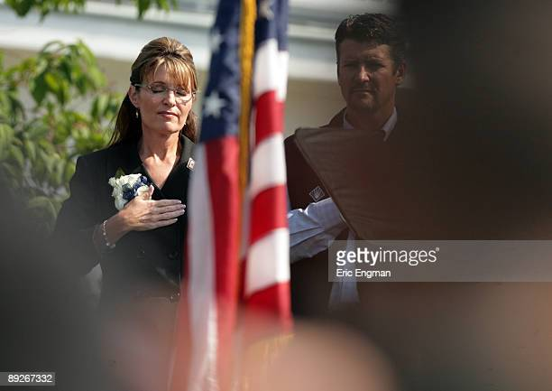 Alaska Governor Sarah Palin covers her heart as the National Anthem is played before she officially resigned during the annual Governor's Picnic July...