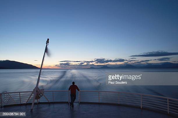 usa, alaska, man standing on back of state ferry, sunset, rear view - ferry stock photos and pictures