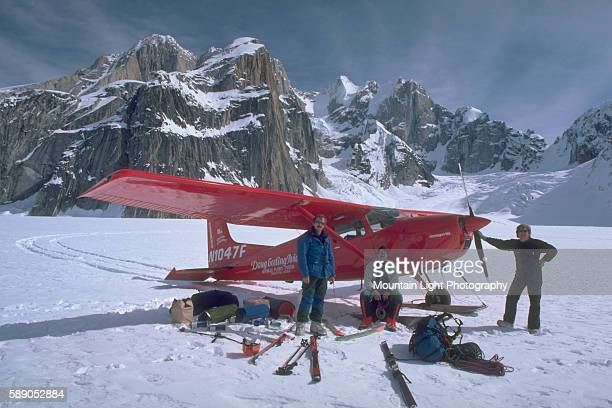 Alaskan Bush Pilot Doug Geeting poses with his small plane and two passengers near a mountain in Alaska.