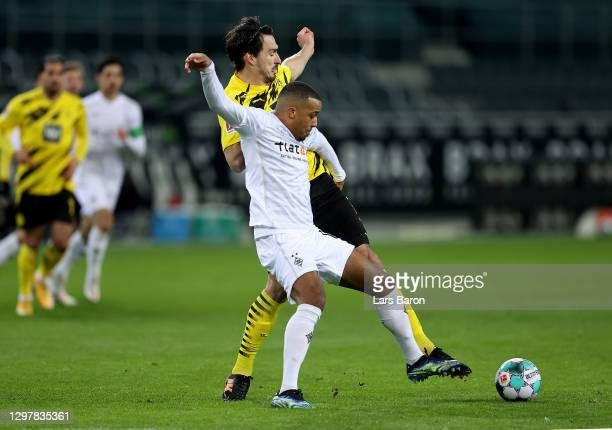 Alassane Pléa of Gladbach challenges Mats Hummels of Dortmund during the Bundesliga match between Borussia Moenchengladbach and Borussia Dortmund at...