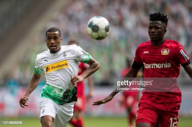 Alassane Plea of Borussia Moenchengladbach and Edmond Tapsoba of Bayer 04 Leverkusen in action during the Bundesliga match between Borussia...
