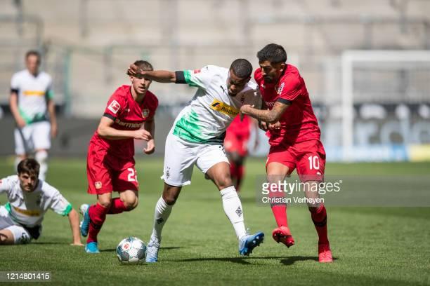 Alassane Plea of Borussia Moenchengladbach and Kerem Demirbay of Bayer 04 Leverkusen battle for the ball during the Bundesliga match between Borussia...