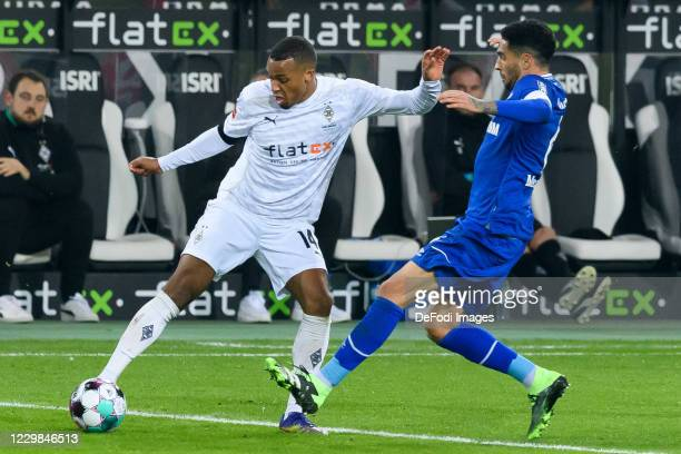Alassane Plea of Borussia Moenchengladbach and Omar Mascarell of FC Schalke 04 battle for the ball during the Bundesliga match between Borussia...