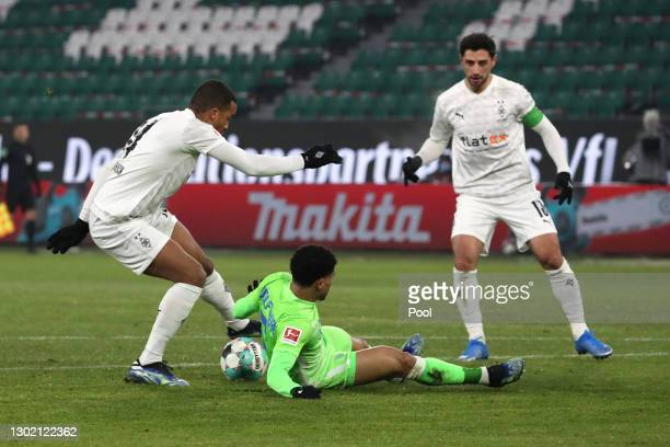 Alassane Plea of Borussia Moenchengladbach and Paulo Otavio of VfL Wolfsburg battle for the ball during the Bundesliga match between VfL Wolfsburg...