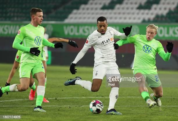 Alassane Plea of Borussia Moenchengladbach is challenged by Xaver Schlager of VfL Wolfsburg during the Bundesliga match between VfL Wolfsburg and...
