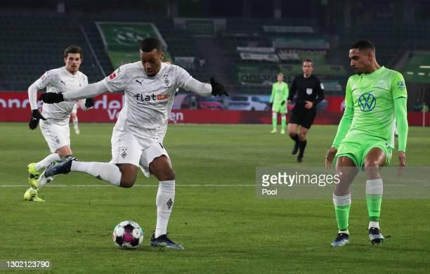Alassane Plea of Borussia Moenchengladbach is put under pressure by Maxence Lacroix of VfL Wolfsburg during the Bundesliga match between VfL...