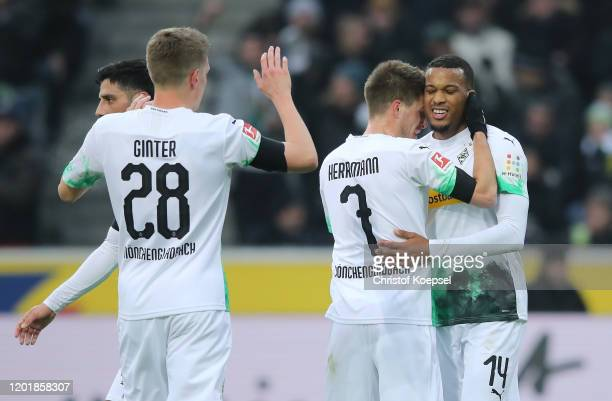 Alassane Plea of Borussia Monchengladbach celebrates after scoring his team's first goal with teammate Patrick Herrmann during the Bundesliga match...