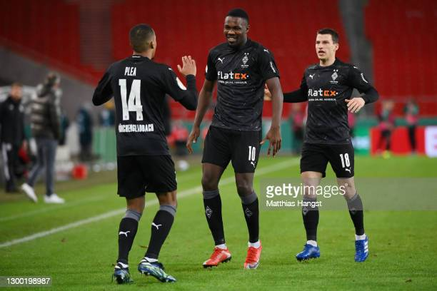 Alassane Plea of Borussia Monchengladbach celebrates with Marcus Thuram and Stefan Lainer after scoring his team's second goal during the DFB Cup...