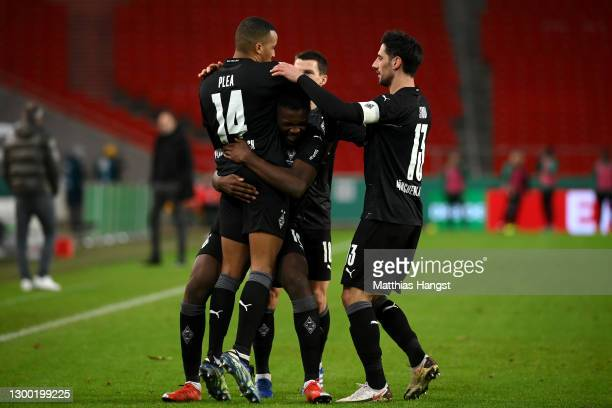Alassane Plea of Borussia Monchengladbach celebrates with team mates Marcus Thuram and Lars Stindl after scoring their side's second goal during the...
