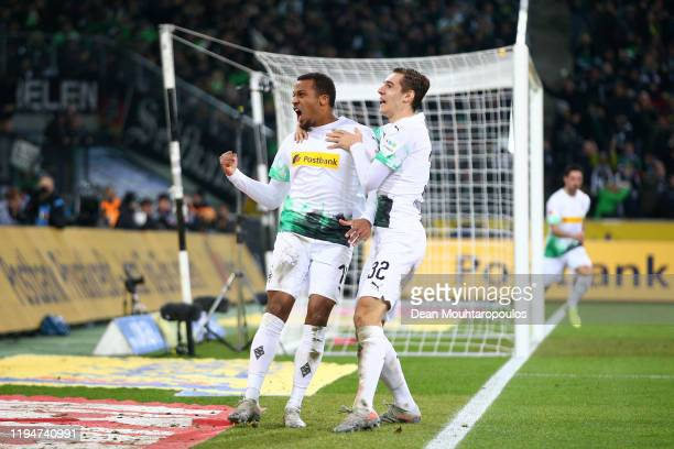 Alassane Plea of Borussia Monchengladbach celebrates with teammate Florian Neuhaus after scoring his team's first goal during the Bundesliga match...