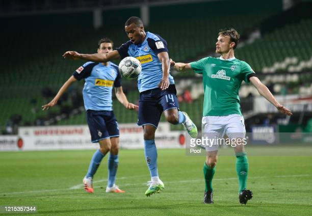Alassane Plea of Borussia Monchengladbach controls the ball under pressure from Christian Gross of SV Werder Bremen during the Bundesliga match...