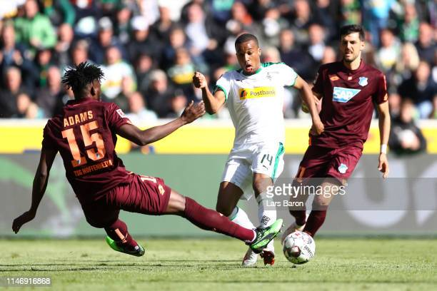 Alassane Plea of Borussia Monchengladbach is challenged by Kasim Adams of 1899 Hoffenheim during the Bundesliga match between Borussia...