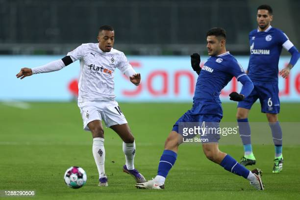 Alassane Plea of Borussia Monchengladbach is challenged by Ozan Kabak of FC Schalke 04 during the Bundesliga match between Borussia Moenchengladbach...