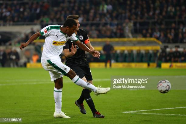Alassane Plea of Borussia Monchengladbach scores his team's first goal past David Abraham of Eintracht Frankfurt during the Bundesliga match between...