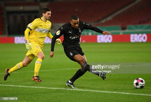 Alassane Plea of Borussia Monchengladbach scores their side's second goal as he is pressured by Fabian Bredlow of VfB Stuttgart during the DFB Cup...