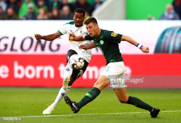 Alassane Plea of Borussia Monchengladbach scors the opening goal past Robin Knoche of VfL Wolfsburg during the Bundesliga match between VfL Wolfsburg...