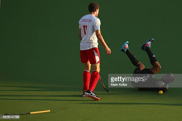 Alastair Brogdon of England looks down at Solomon Eccles of Trinidad and Tobago after he fell in a tackle during the Men's preliminary match between...