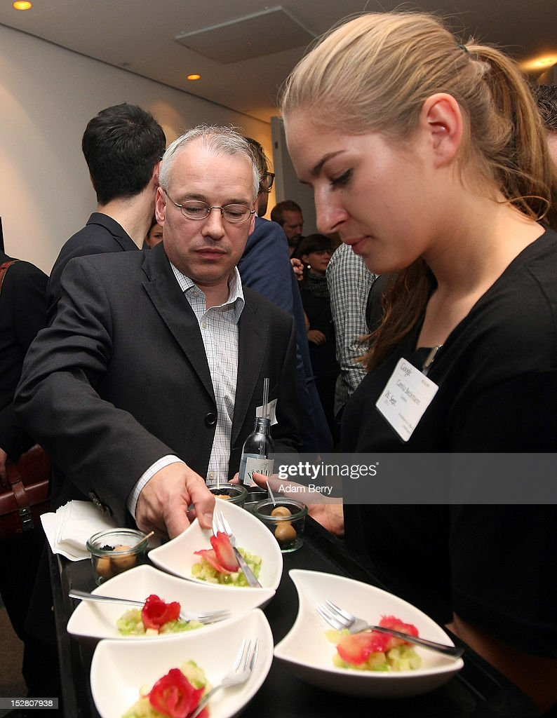 Alastair Bruce, sales director at Google Germany (L), takes a plate of cucumbers and salmon on September 26, 2012 at the official opening party of the Google offices in Berlin, Germany. Although the American company holds 95% of the German search engine market share and already has offices in Hamburg and Munich, its new offices on the prestigious Unter den Linden avenue are its first in the German capital. The Internet giant has been met with opposition in the country recently by the former president's wife, who has sued it based on search results for her name that she considers derogative. The European Commission has planned new data privacy regulations in a country where many residents opted in to have their homes pixeled out when the company introduced its Street View technology.