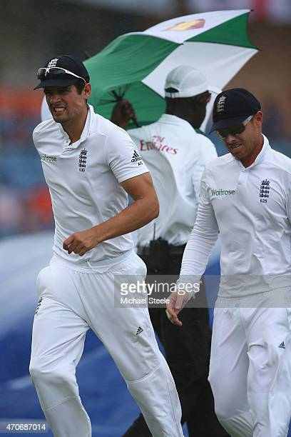 Alastair Cook and Ian Bell of England run towards the dressing room as rain stops play during day two of the 2nd Test match between West Indies and...