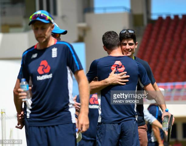 Alastair Cook hugs James Anderson of England while Joe Root sips water during a training session one day ahead of the 2nd Test between West Indies...