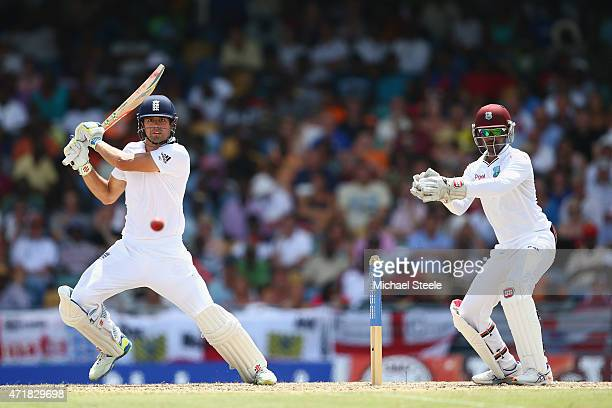 Alastair Cook of England cuts a delivery off the bowling of Marlon Samuels of West Indies as wicketkeeper Denesh Ramdin looks on during day one of...