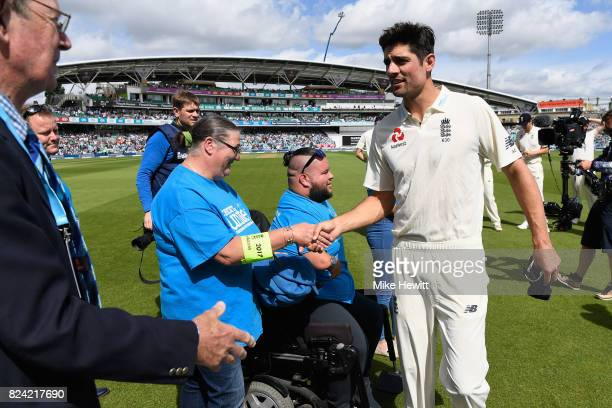 Alastair Cook of England greets representatives from the Cricket United charity during Day Three of the 3rd Investec Test match between England and...