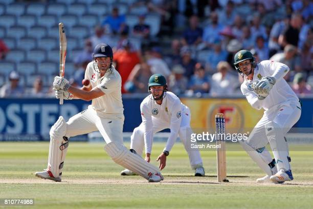 Alastair Cook of England hits out as South Africa wicket keeper Quinton de Kock and fielder Theunis de Bruyn look on during the 1st Investec Test...