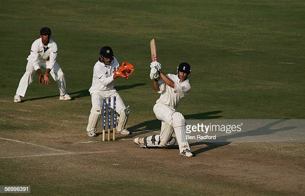 Alastair Cook of England hits out during his maiden test century as Wicketkeeper Mahendra Dhoni and Rahul Dravid look on during the day four of the...