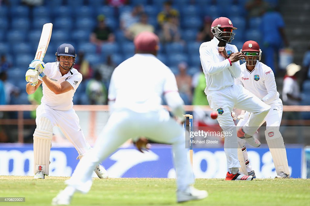 Alastair Cook of England hits to the offside as wicketkeeper Denesh Ramdin and Jermaine Blackwood of West Indies look on during day three of the 2nd Test match between West Indies and England at the National Cricket Stadium in St George's on April 23, 2015 in Grenada, Grenada.