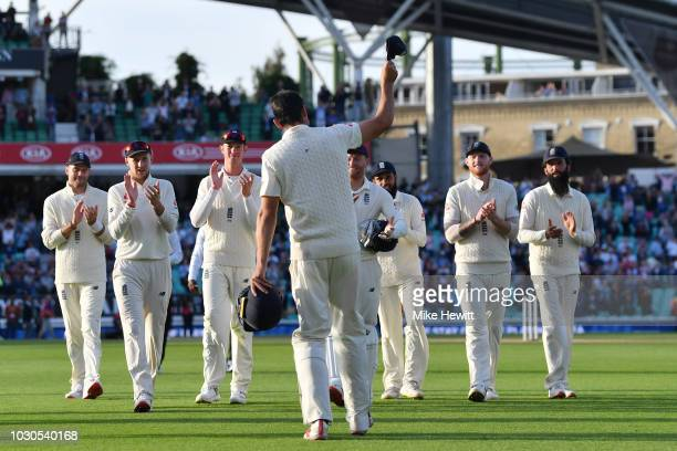Alastair Cook of England is applauded off the pitch by his teammates at the end of the Specsavers 5th Test Day Four between England and India at The...