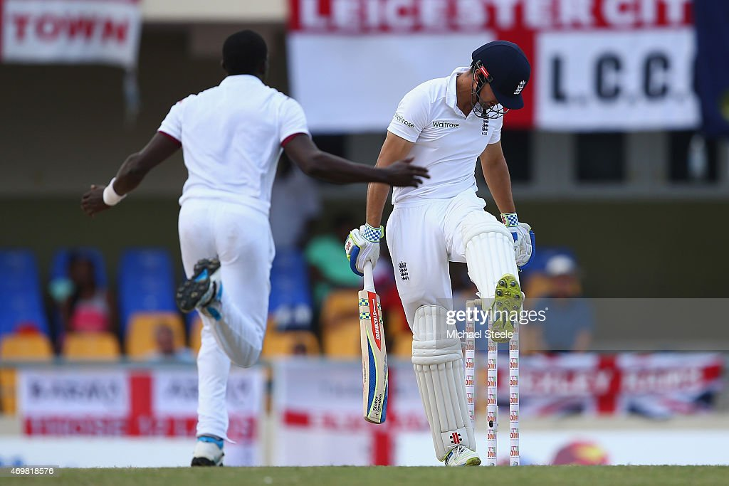 Alastair Cook (R) of England kicks out in frustration after being dismissed for 13 runs caught by Sulieman Benn off the bowling of Jerome Taylor (L) of West Indies during day three of the 1st Test match between West Indies and England at the Sir Vivian Richards Stadium on April 15, 2015 in Antigua, Antigua and Barbuda.