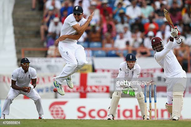 Alastair Cook of England leaps to avoid a cover drive from Marlon Samuels of West Indies during day one of the 2nd Test match between West Indies and...