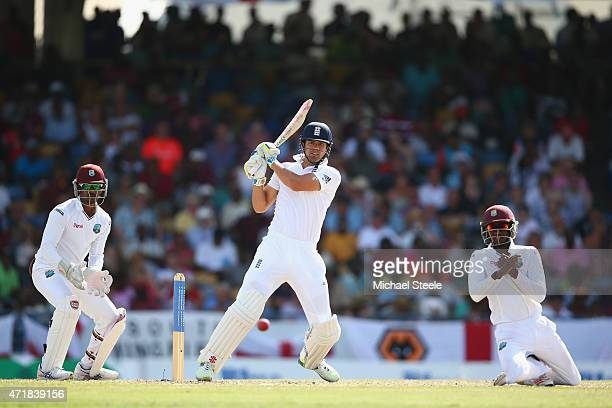 Alastair Cook of England pulls to the legside as Jermaine Blackwood of West Indies takes cover and wicketkeeper Denesh Ramdin looks on during day one...