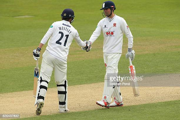 Alastair Cook of Essex celebrates reaching a century of runs with Tom Westley during day two of the Specsavers County Championship match between...