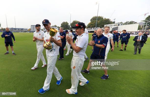 Alastair Cook of Essex lifts the County Championship trophy during day three of the Specsavers County Championship Division One match between Essex...