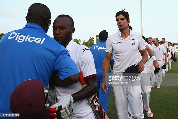 Alastair Cook the captain of England shakes the opponents hands alongside Jermaine Blackwood of West Indies after losing the match and drawing the...