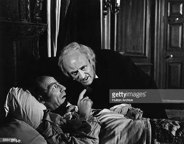 Alastair Sim as Scrooge listens to the words of a dying man