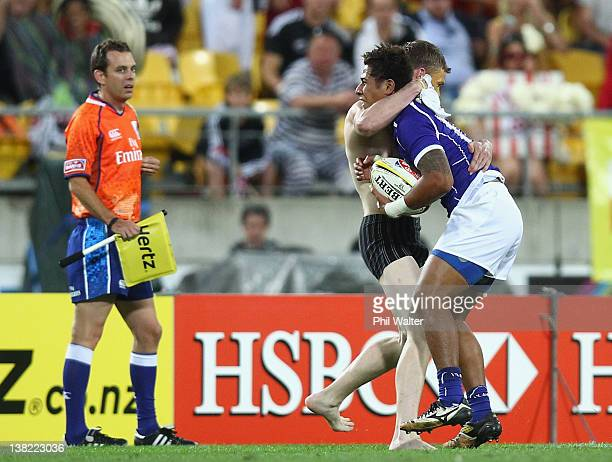 Alatasi Tupou of Samoa is tackled by a streaker during the game between Samoa and New Zealand on day one of the Wellington Sevens at Westpac Stadium...