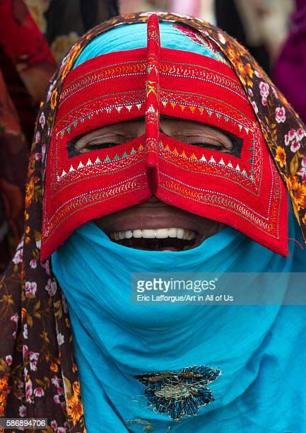 Alaughing bandari woman wearing a traditional mask called the burqa at panjshambe bazar thursday market hormozgan minab Iran on December 31 2015 in...