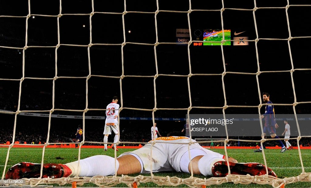 TOPSHOT - Alaves' Chilean defender Guillermo Maripan lies in the goal after Barcelona's Uruguayan forward Luis Suarez's score during the Spanish league football match between FC Barcelona and Deportivo Alaves at the Camp Nou stadium in Barcelona on January 28, 2018. / AFP PHOTO / Josep LAGO