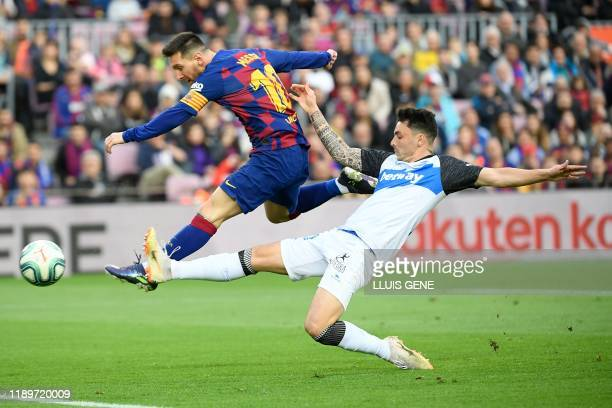 Alaves' Spanish defender Ximo Navarro challenges Barcelona's Argentine forward Lionel Messi during the Spanish league football match FC Barcelona...